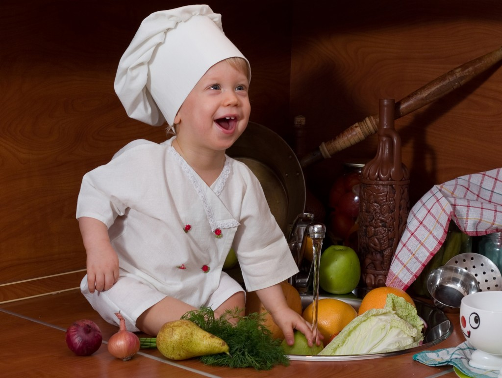 laughing little boy in the cook costume at the kitchen with vegetables