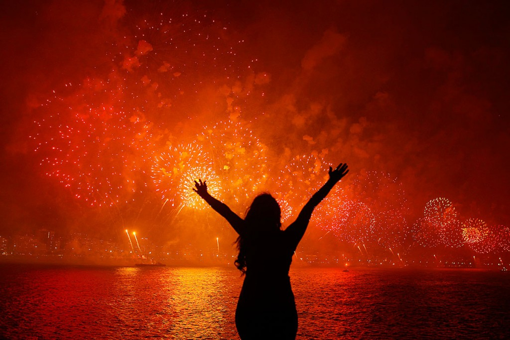 A woman celebrates the New Year as she watches fireworks exploding above Copacabana beach in Rio de Janeiro January 1, 2013. More than two million people gathered along Rio's most famous beach to witness the 20-minute display and celebrate the beginning of a new year. REUTERS/Pilar Olivares (BRAZIL - Tags: ANNIVERSARY SOCIETY TPX IMAGES OF THE DAY)